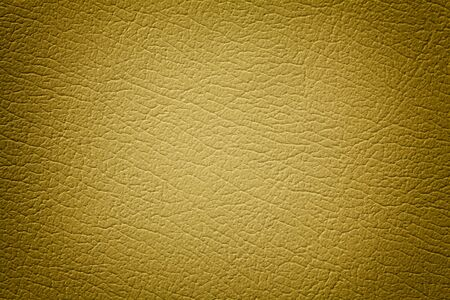 Dark yellow leather texture background, closeup. Golden cracked backdrop from wrinkle skin, structure of textile with vignette. Stockfoto