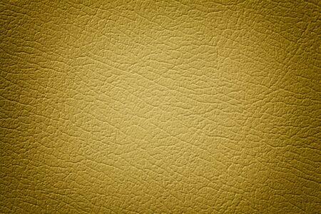 Dunkelgelber Lederbeschaffenheitshintergrund, Nahaufnahme. Goldener rissiger Hintergrund aus Faltenhaut, Textilstruktur mit Vignette. Standard-Bild
