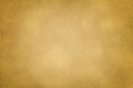 Golden matte background of suede fabric, closeup. Velvet texture of seamless yellow leather with vignette.