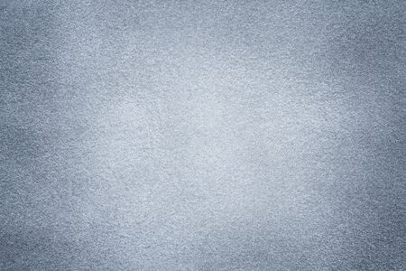 Background of light gray suede fabric closeup. Velvet matt texture of silver nubuck textile with dark vignette.