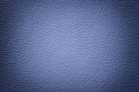 Navy blue leather texture background, closeup. Denim cracked backdrop from wrinkle skin, structure of textile with vignette. Фото со стока