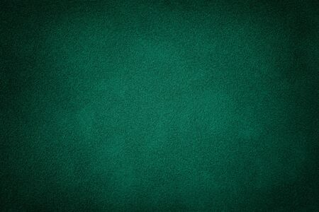 Dark green matte background of suede fabric, closeup. Velvet texture of seamless deep emerald leather. Felt material macro with vignette. Фото со стока