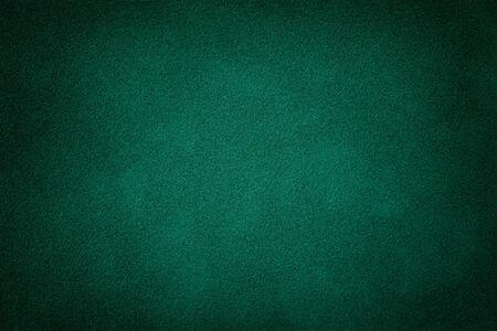 Dunkelgrüner matter Hintergrund aus Wildleder, Nahaufnahme. Samtstruktur aus nahtlosem tiefem Smaragdleder. Filzmaterial Makro mit Vignette.