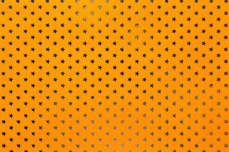 Fondo naranja de papel de aluminio con un patrón de primer plano de estrellas brillantes plateadas. Textura de la superficie del papel de vacaciones de envoltura metalizada de color amarillo brillante.