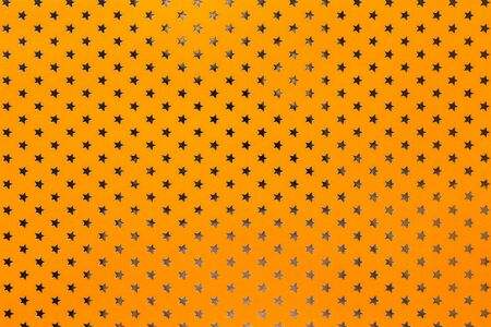 Orange background from metal foil paper with a pattern of silver sparkling stars closeup. Texture of bright yellow metallized wrapping holiday paper surface.