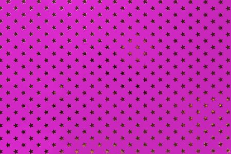 Dark purple background from metal foil paper with a pattern of sparkling golden stars, closeup. Texture of magenta metallized wrapping holiday paper surface.