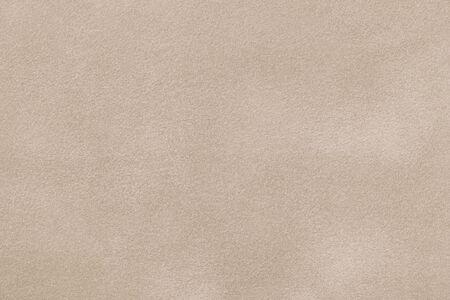 Hellbeige Matthintergrund aus Wildleder, Nahaufnahme. Samtstruktur aus nahtlosem Sandleder. Standard-Bild