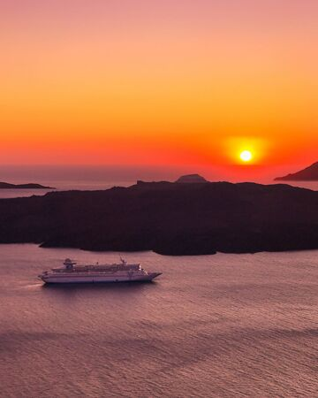 Sunset in Santorini, Greece and cruise ship in the sea, against the backdrop of the setting sun and volcanic rocks 스톡 콘텐츠