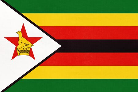 Republic of Zimbabwe national fabric flag, textile background. Symbol of international world African country. State zimbabwean official sign. 스톡 콘텐츠
