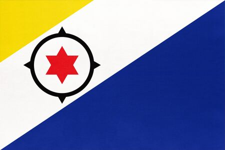 Bonaire island national fabric flag, textile background. Symbol of international caribbean sea world country. American and Netherlands state official sign. Imagens