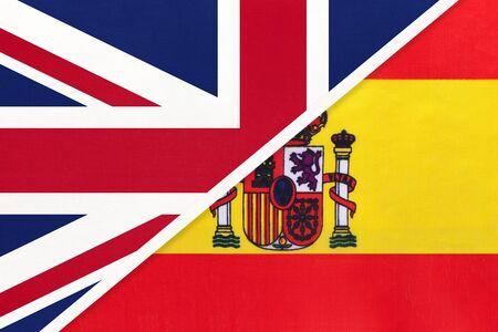 United Kingdom of Great Britain and Ireland vs Spain national flag from textile. Relationship, partnership and economic between two european countries. Banque d'images