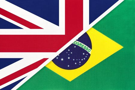 United Kingdom of Great Britain and Ireland vs Republic of Brazil national flag from textile. Relationship, partnership and economic between two european and south american countries.