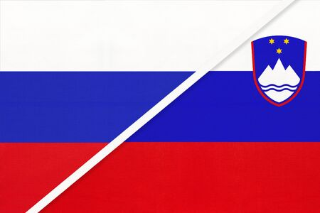 Russia or Russian Federation vs Republic of Slovenia national flag from textile. Relationship, partnership and economic between two european and asian countries.