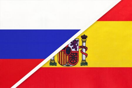 Russia or Russian Federation vs Kingdom of Spain national flag from textile. Relationship, partnership and economic between two european and asian countries.
