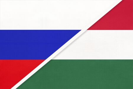 Russia or Russian Federation vs Hungary national flag from textile. Relationship, partnership and economic between two european and asian countries.