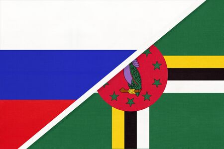 Russia or Russian Federation vs Commonwealth of Dominica national flag from textile. Relationship, partnership and economic between two european and american countries. Banco de Imagens