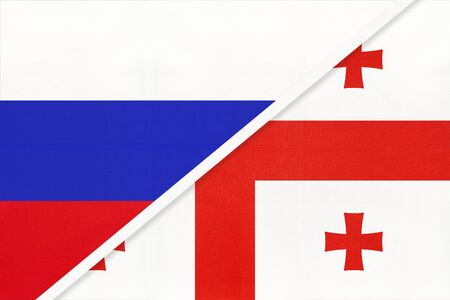 Russia or Russian Federation vs Republic of Georgia national flag from textile. Relationship, partnership and economic between two european and asian countries.