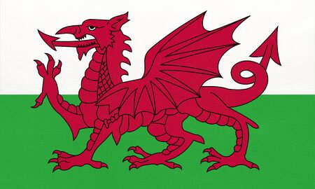 Wales national fabric flag, textile background. Symbol of part of United kingdom international world country. England welsh official sign.