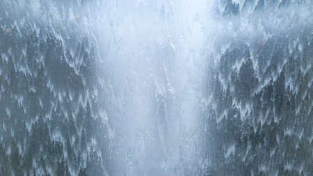 Powerful flow of waterfall, closeup. Background from wave nature water stream, macro view. Tropical pattern for relax. Wall fountain.