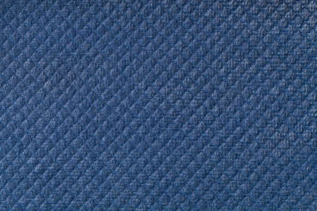 Texture of navy blue fluffy fabric background with rhomboid pattern, macro. Abstract backdrop from decorative denim woven textile material.