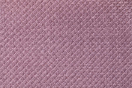 Texture of light purple fluffy fabric background with rhomboid pattern, macro. Abstract backdrop from decorative pink woven textile material.