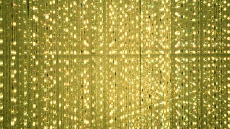 Golden background of LED flashing, blinking and flickering bulbs. Disco and holiday illuminated neon shiny backdrop. Abstract yellow wall decoration from twinkle garland for concert.