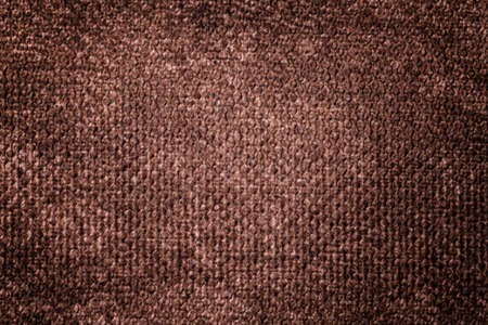 Dark brown background from a soft textile material. sheathing fabric with natural texture. Cloth backdrop with vignette.