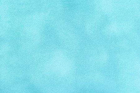 Light blue matte background of suede fabric, closeup. Velvet texture of seamless denim textile, macro. Structure of sky felt canvas backdrop.