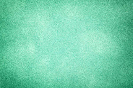 Dark green matte background of suede fabric with vignette, closeup. Velvet texture of seamless cyan textile with gradient, macro. Structure of emerald felt canvas backdrop.