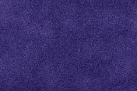Navy blue matte background of suede fabric, closeup. Velvet texture of seamless indigo textile, macro. Structure of felt canvas backdrop.