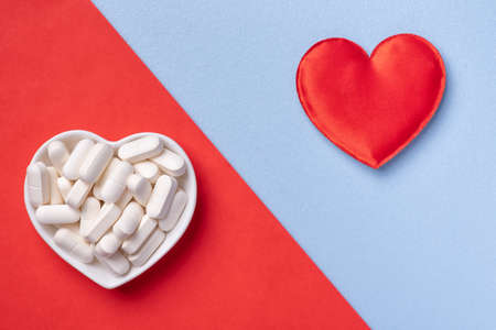 Pills in bowl and red heart on blue and red background. Medicines for cardiology health treatment and diseases. Standard-Bild