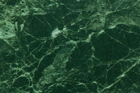 Texture of dark green and olive marble for tabletop with light lines of pattern, macro background. Emerald stone countertop from mineral tile for covering table, abstract backdrop closeup.