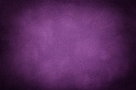 Dark purple matte background of suede fabric with vignette, closeup. Velvet texture of seamless violet textile with gradient, macro. Structure of lavender felt canvas backdrop.