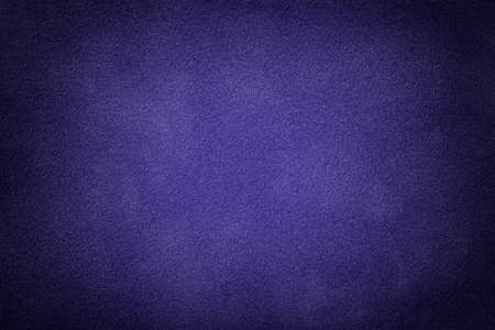 Navy blue matte background of suede fabric with vignette, closeup. Velvet texture of seamless indigo textile with gradient, macro. Structure of violet felt canvas backdrop.