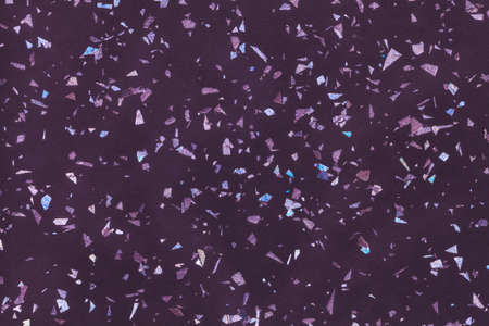 Dark purple sparkling background from small foil sequins, closeup. Violet texture backdrop with small crumb pattern for interior design and kitchen countertop.