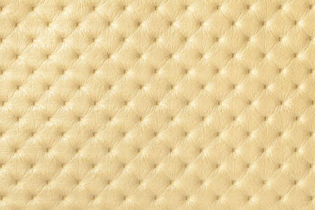 Texture of light yellow leather background with capitone pattern, macro. Golden textile of retro Chesterfield style. Vintage fabric backdrop.