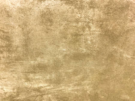 Texture decorative light beige plaster imitating old peeling wall. Obsolete cracked golden stone background with pattern. Structure of brown cement wall.