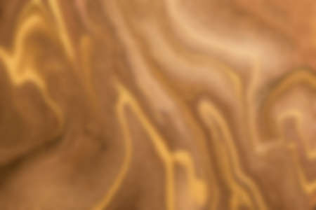 Blurred dark brown and golden background with wavy pattern. Defocused art abstract beige gradient backdrop with blur and bokeh. Blurry wallpaper.