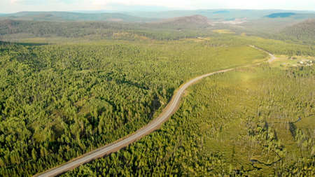 Aerial panoramic view from drone of rural village among fields, forests, river and hills. Countryside landscape and nature on sunset. Empty road and highway, birds eye view. Open space.