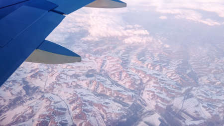 Air plane flies among the clouds over snowy capped mountains. Winter aerial landscape on sunset, view of the wing from the aircraft window.