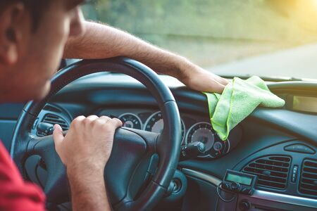 rag wheel: Cleaning with green microfiber cloth polishing car, interior concept