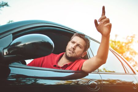outraged: The young man driving the car angry, stuck in a traffic jam