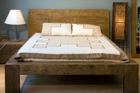 Bedroom with old-style wooden bed Standard-Bild