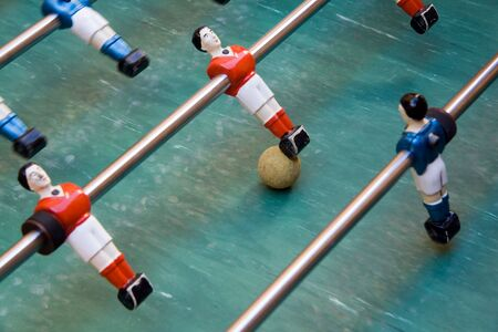 Detail of foosball table with toy players and yellow ball photo