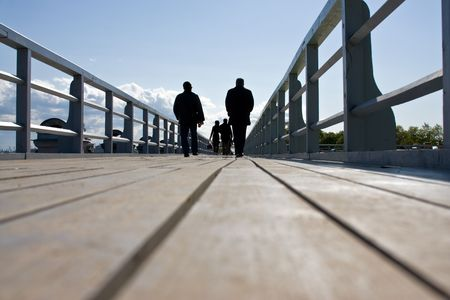 sidewalk talk: Silhuettes of two people walking at the bridge