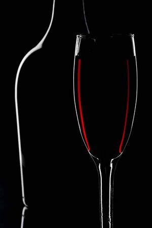 Wine glass and bottle isolated on black background photo
