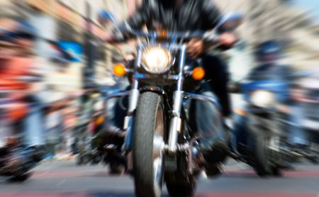 motorcyclist: blurred bike riders rushing at city streeet