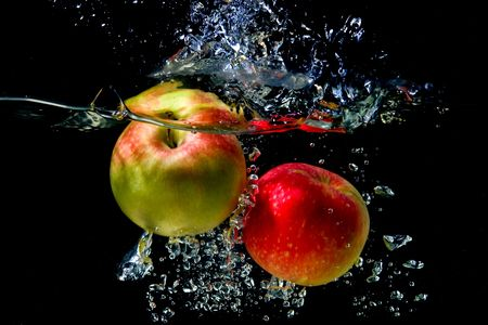 Apples falling to the water with splash and drops photo