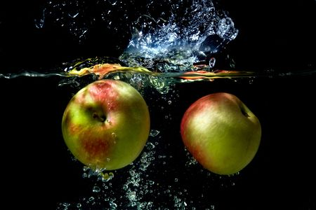 Apples falling to the water with splash and drops