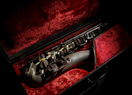 Old saxophone in a case with red background Standard-Bild